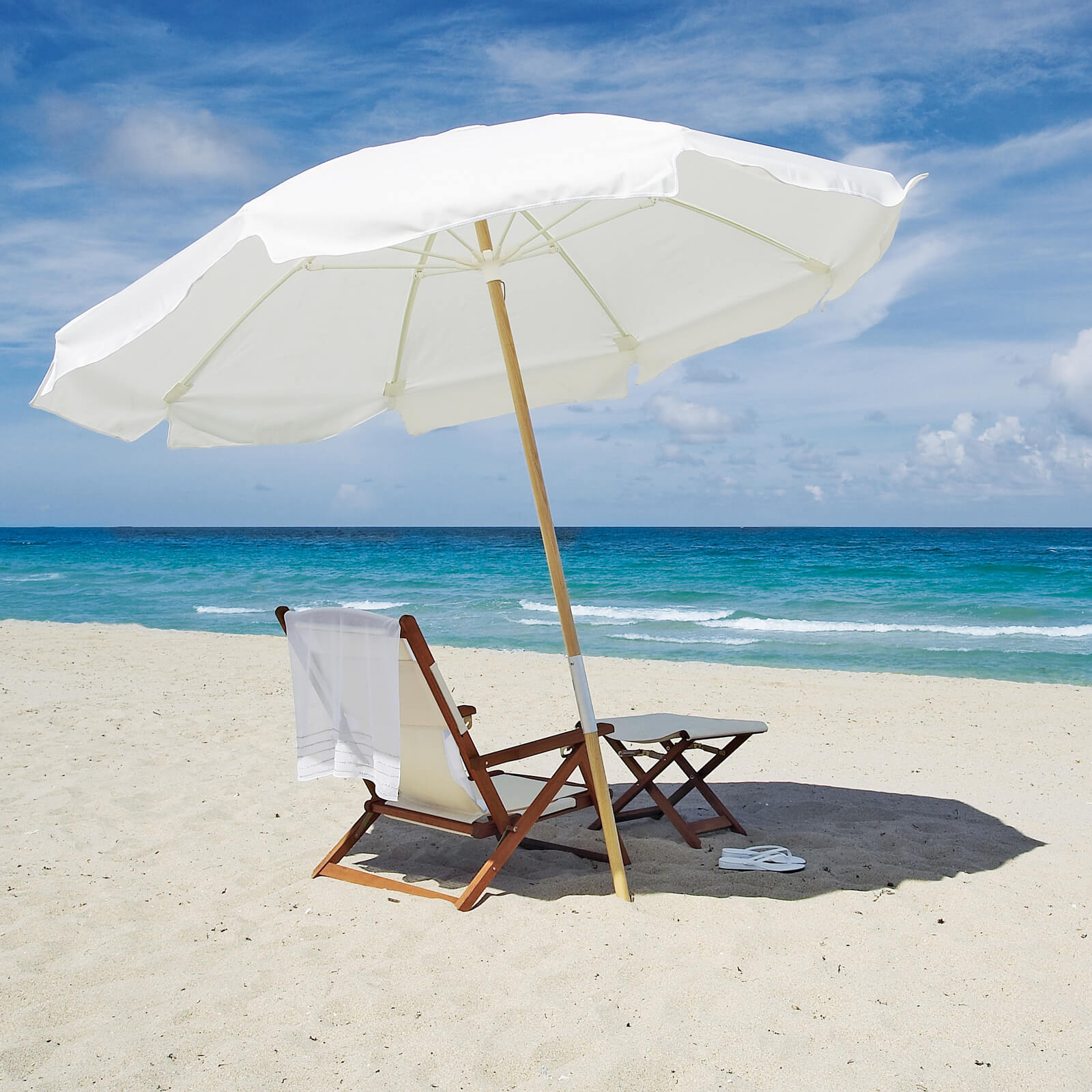 Beach house view of lounge chair and white umbrella.